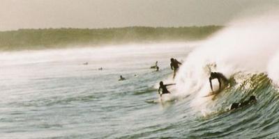 Dos grandes olas arrastran a un grupo de espectadores de un torneo de surf en California